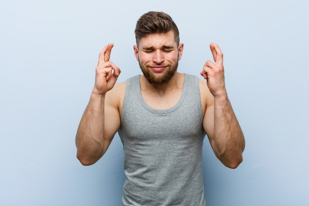 Young handsome fitness man crossing fingers for having luck