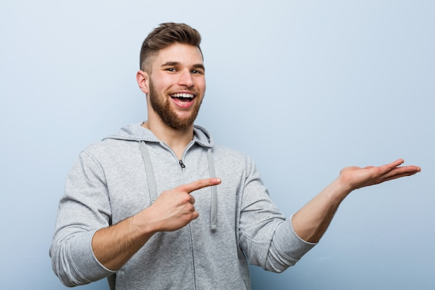 Young handsome fitness man excited holding a copy space on palm.