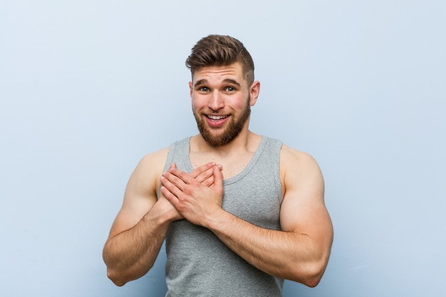 Young handsome fitness man has friendly expression, pressing palm to chest