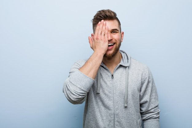 Young handsome fitness man having fun covering half of face with palm.