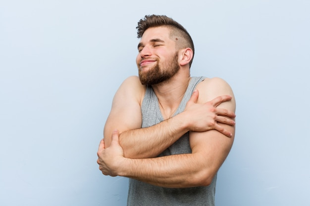 Young handsome fitness man hugs himself, smiling carefree and happy.
