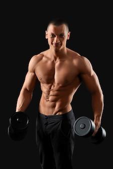 Молодой красавец фитнес позирует с гантелями