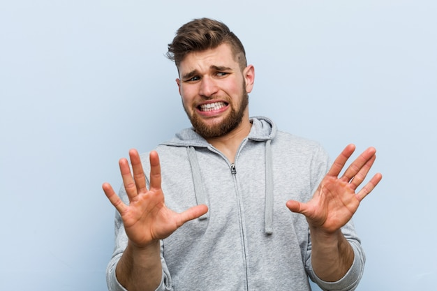 Young handsome fitness man rejecting someone showing a gesture of disgust.