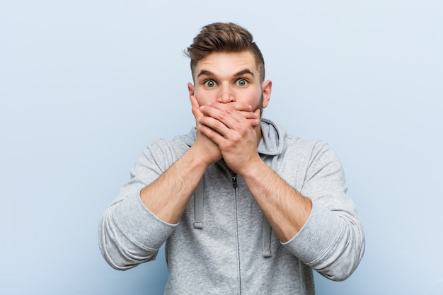 Young handsome fitness man shocked covering mouth with hands.