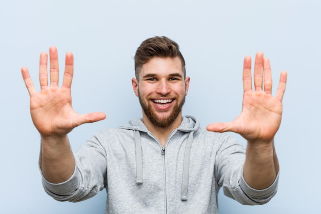 Young handsome fitness man showing number ten with hands.