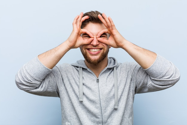 Young handsome fitness man showing okay sign over eyes