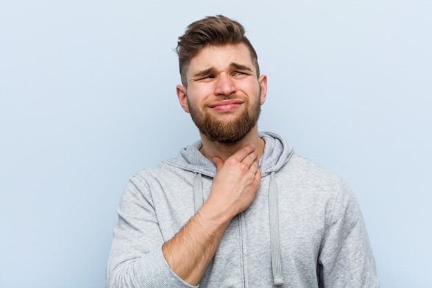 Young handsome fitness man suffers pain in throat due a virus or infection.