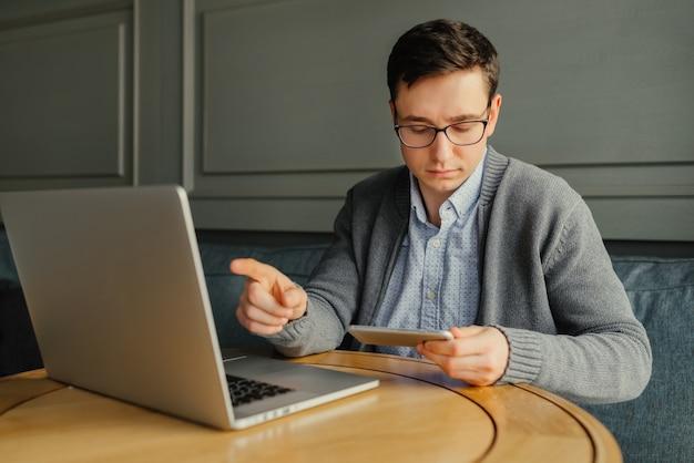 Giovani freelancer belli alla ricerca di informazioni importanti, lavorando con laptop moderni