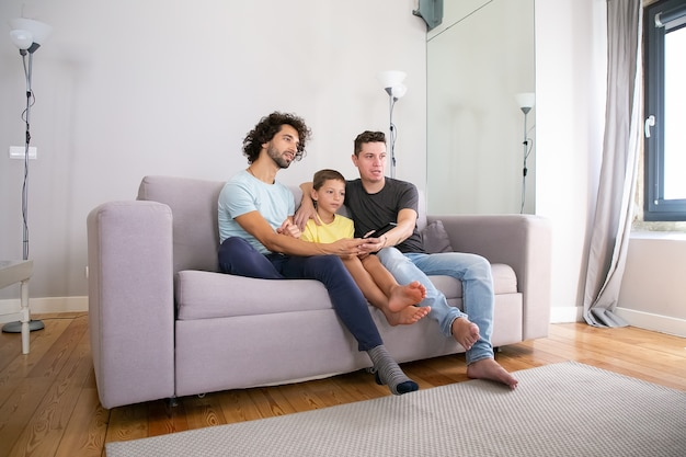 Young handsome gay couple and their son watching tv show at home, sitting on couch in living room, hugging, using remote control, looking away. family and home entertainment concept
