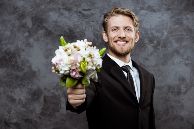 Young handsome groom smiling, holding bridal bouquet