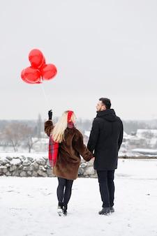 발렌타인 데이에 산책하는 풍선과 함께 젊은 잘 생긴 남자와 여자