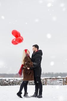 Молодой красивый парень и женщина с воздушными шарами гуляют в день святого валентина