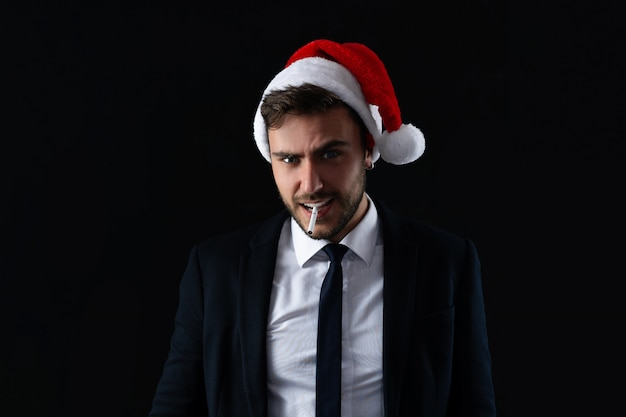 Young handsome guy in business suit and santa hat stands on gray background in studio with serious face and smoking cigarette portrait business person with christmas mood holiday banner