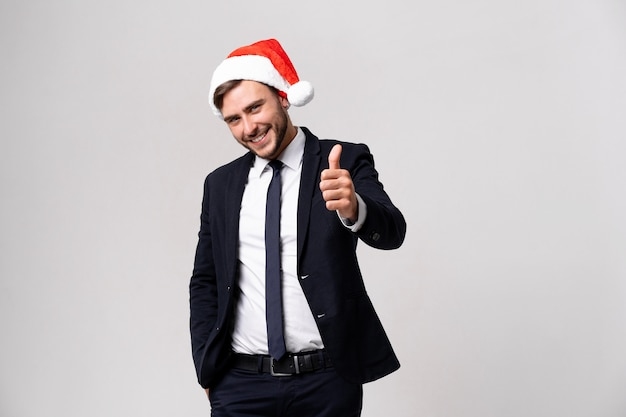Young handsome guy in business suit and santa hat on white background in studio smilie and showing thumbs up two hands. close up portrait business person with christmas mood holiday banner