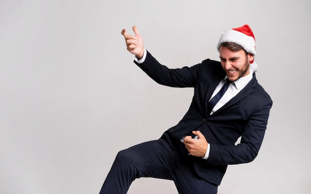 Young handsome guy in business suit and santa hat