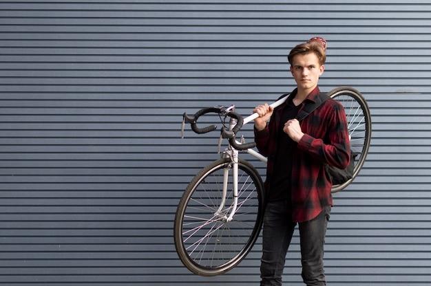 Молодой красивый парень несет сломанный велосипед на плечах у стены, студент идет пешком