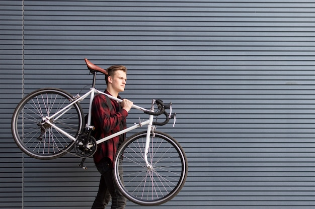 Young handsome guy carries a broken bike on his shoulders against the wall