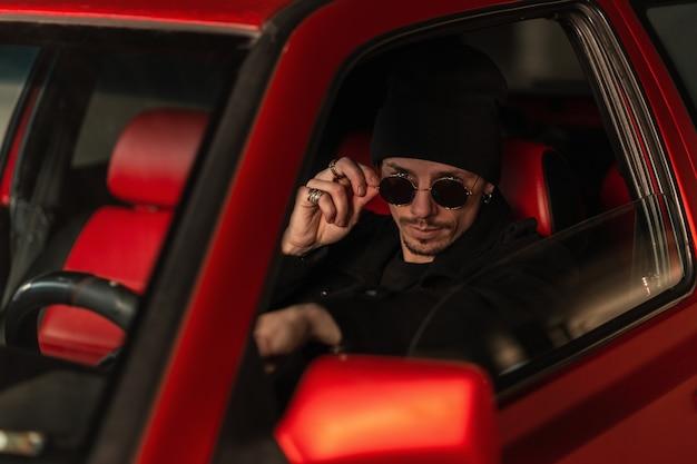 젊고 잘생긴 남자 운전자는 선글라스를 통해 보고 차를 운전한다