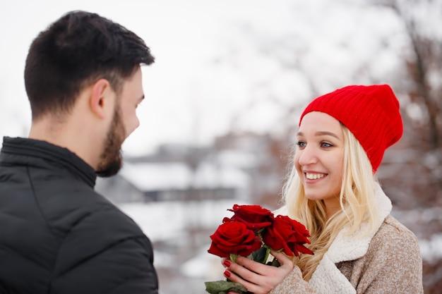 발렌타인 데이에 소녀에게 장미 꽃다발을주는 젊은 잘 생긴 남자