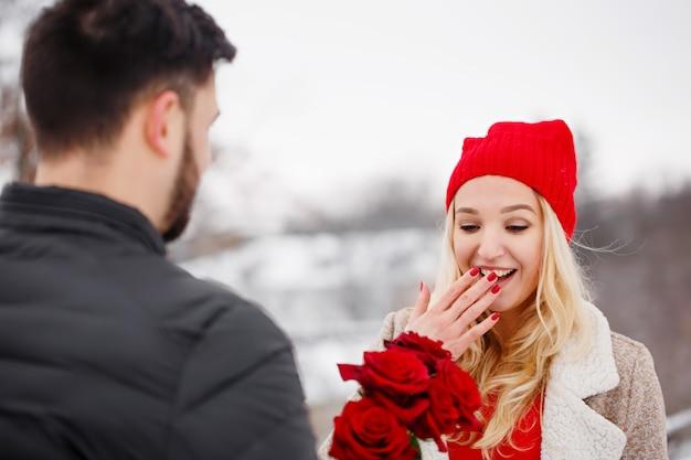 발렌타인 데이에 여자에게 장미 꽃다발을주는 젊은 잘 생긴 남자