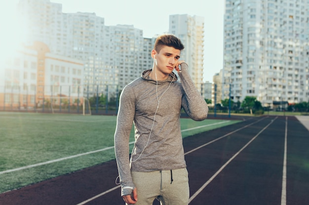 Young handsome guy in gray sport suit on running track on buildings background in the morning. he wears gray sport suit, headphones. he is looking to side.