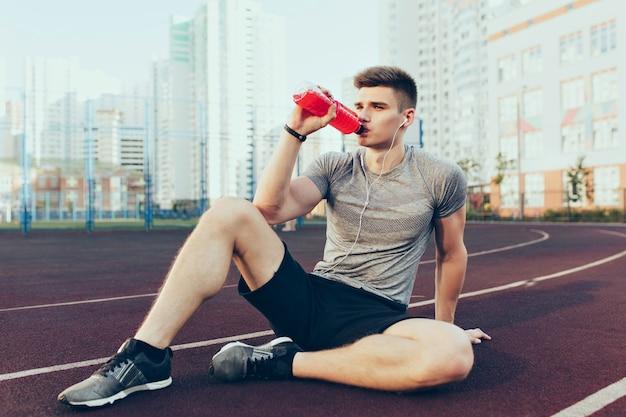 Молодой красивый парень утром отдыхает на стадионе. он носит спортивную одежду, слушает музыку через наушники, пьет красный напиток из бутылки.