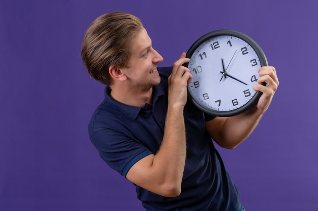 Young handsome guy holding clock in hands looking at it with happy face exited and joyful standing over purple background