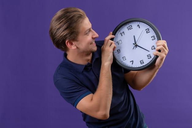 Giovane ragazzo bello che tiene l'orologio nelle mani guardandolo con la faccia felice uscito e gioioso in piedi su sfondo viola