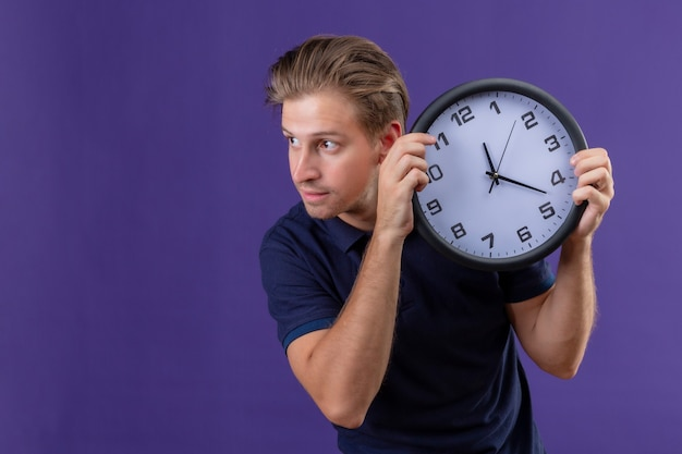 紫色の背景の上に立って自信を持って式とよそ見時計を保持している若いハンサムな男