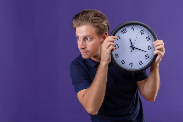 Orologio della holding del giovane bel ragazzo che osserva da parte con espressione fiduciosa in piedi su sfondo viola