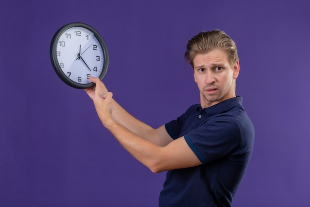 Young handsome guy holding clock looking at camera with confuse expression standing over purple background