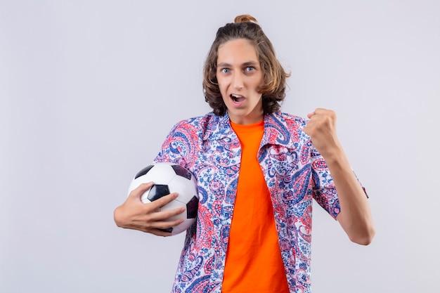 Giovane ragazzo bello che tiene il pallone da calcio guardando uscito rallegrandosi del suo successo e della vittoria stringendo i pugni con gioia felice di raggiungere il suo scopo e obiettivi in piedi su sfondo bianco