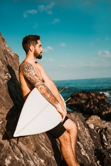Young handsome guy holding surf board near stones