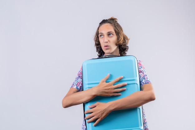 旅行のスーツケースを抱いて肯定的で幸せな立っている若いハンサムな男