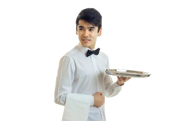 그릇의 쟁반을 들고 웃 고 흰 벽에 고립 된 셔츠에 젊은 잘 생긴 남자