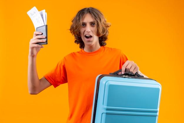 Молодой красивый парень в оранжевой футболке с авиабилетами и дорожным чемоданом выглядит удивленным, стоя на желтом фоне