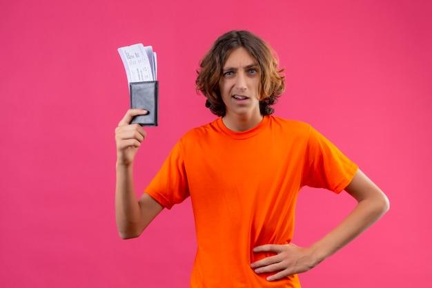 Молодой красивый парень в оранжевой футболке с билетами на самолет и недовольством стоит на розовом фоне