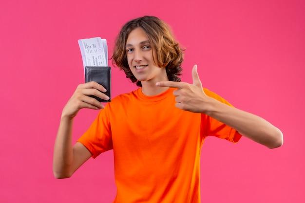 Молодой красивый парень в оранжевой футболке с билетами на самолет выглядит уверенно, указывая пальцем на него, весело улыбаясь, стоя на розовом фоне
