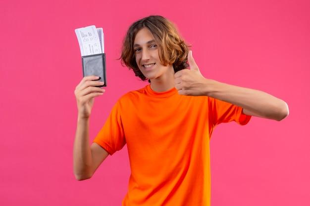 Молодой красивый парень в оранжевой футболке, держащий авиабилеты, выглядит уверенно, показывает палец вверх, весело улыбаясь, стоя на розовом фоне