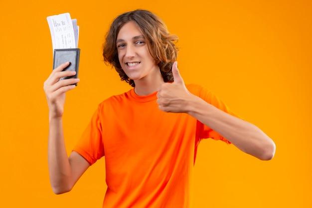 Молодой красивый парень в оранжевой футболке с билетами на самолет выглядит уверенно, показывает палец вверх, весело улыбаясь, стоя на желтом фоне