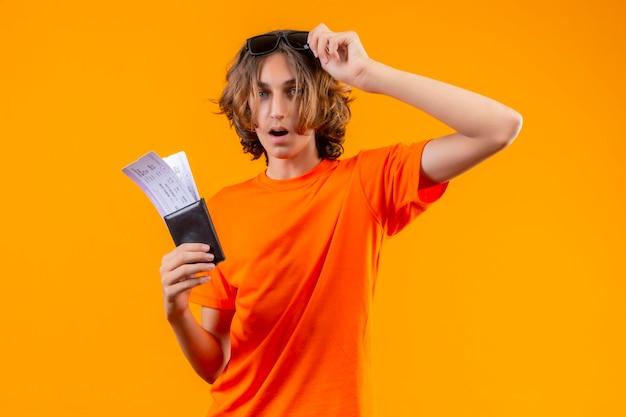 Молодой красивый парень в оранжевой футболке с билетами на самолет, снимая очки, выглядит удивленным и изумленным, стоя на желтом фоне