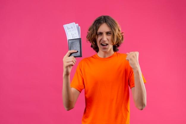 Молодой красивый парень в оранжевой футболке держит авиабилеты, поднимая кулак после победы, счастливый и позитивный улыбающийся, бодро стоя на розовом фоне