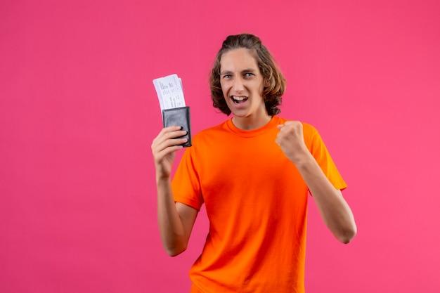 Молодой красивый парень в оранжевой футболке, держащий авиабилеты, поднимает кулак, весело улыбаясь, концепция победителя стоит на розовом фоне