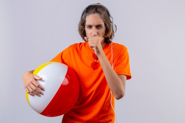 白い背景の上に立って体調不良の咳をしてヘッドフォンでインフレータブルボールを保持しているオレンジ色のtシャツの若いハンサムな男