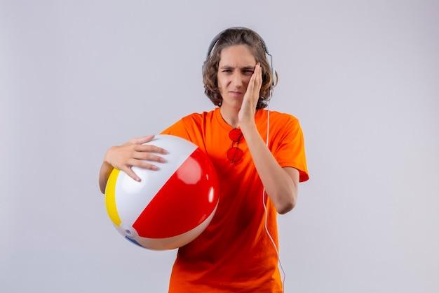 흰색 배경 위에 서있는 치통을 갖는 불쾌한 감동 뺨을 찾고 헤드폰으로 풍선 공을 들고 오렌지 티셔츠에 젊은 잘 생긴 남자