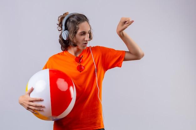 自信を持って立っている上腕二頭筋を示す拳を上げるヘッドフォンでインフレータブルボールを保持しているオレンジ色のtシャツの若いハンサムな男