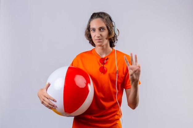 흰색 배경 위에 서 웃 고 3 번을 보여주는 헤드폰으로 풍선 공을 들고 오렌지 티셔츠에 젊은 잘 생긴 남자
