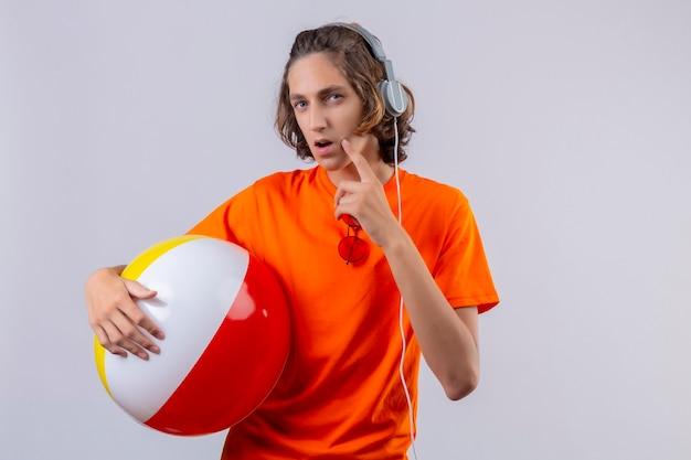 Молодой красивый парень в оранжевой футболке держит надувной мяч в наушниках, стоя с задумчивым взглядом, неуверенно глядя на белом фоне