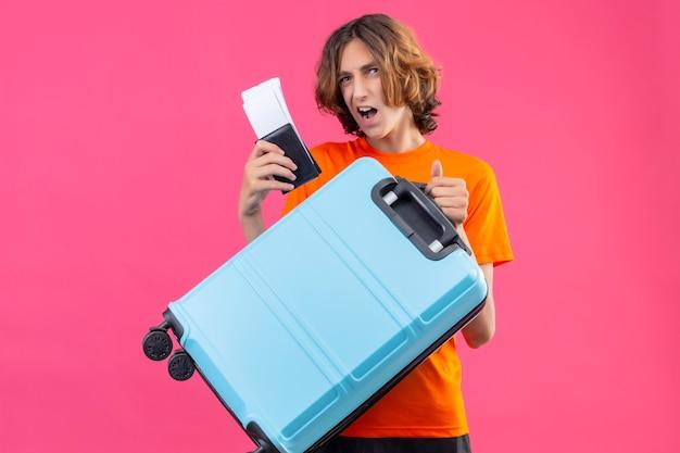 Молодой красивый парень в оранжевой футболке, держащий дорожный чемодан и авиабилеты, жизнерадостно позитивно и счастливо улыбается, стоя на розовом фоне