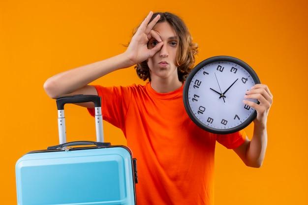 Молодой красивый парень в оранжевой футболке держит дорожный чемодан и часы, делающие хорошо, знак рукой, глядя сквозь этот знак с уверенным серьезным выражением лица, стоящим на желтом фоне